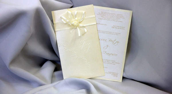 Invitación en forma vertical, en cartulina nacarada color crema, texto impreso en color ocre. El sobre lleva flores e iniciales al relieve y cinta organza al tono.