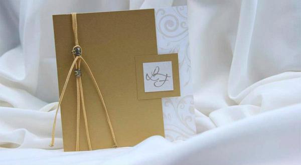 Elegante tarjeta en cartulina perlada, con diseños en color beige en su interior. Está cubierta en cartulina dorada, y el detalle final los dan los cordones y apliques al tono.