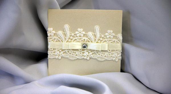 Varios tonos de beige en diferentes materiales: Cartulina perlada, guipur, raso y un cristal en destaque, demuestran en esta tarjeta de boda un trabajo delicado en cada pieza.