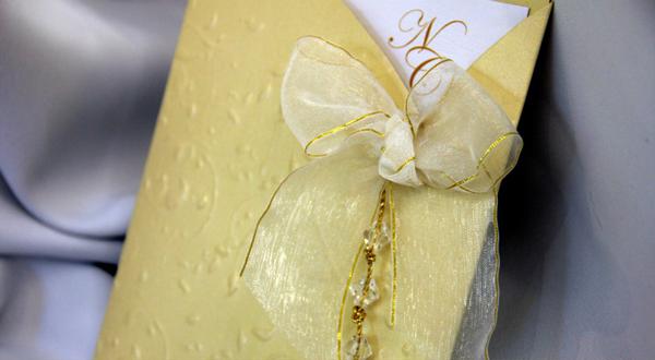 El dorado es un tono que siempre va de la mano con el beige. En este caso, se torna protagonista el sobre color oro, con relieves y apliques de lazo en organza y cristales.